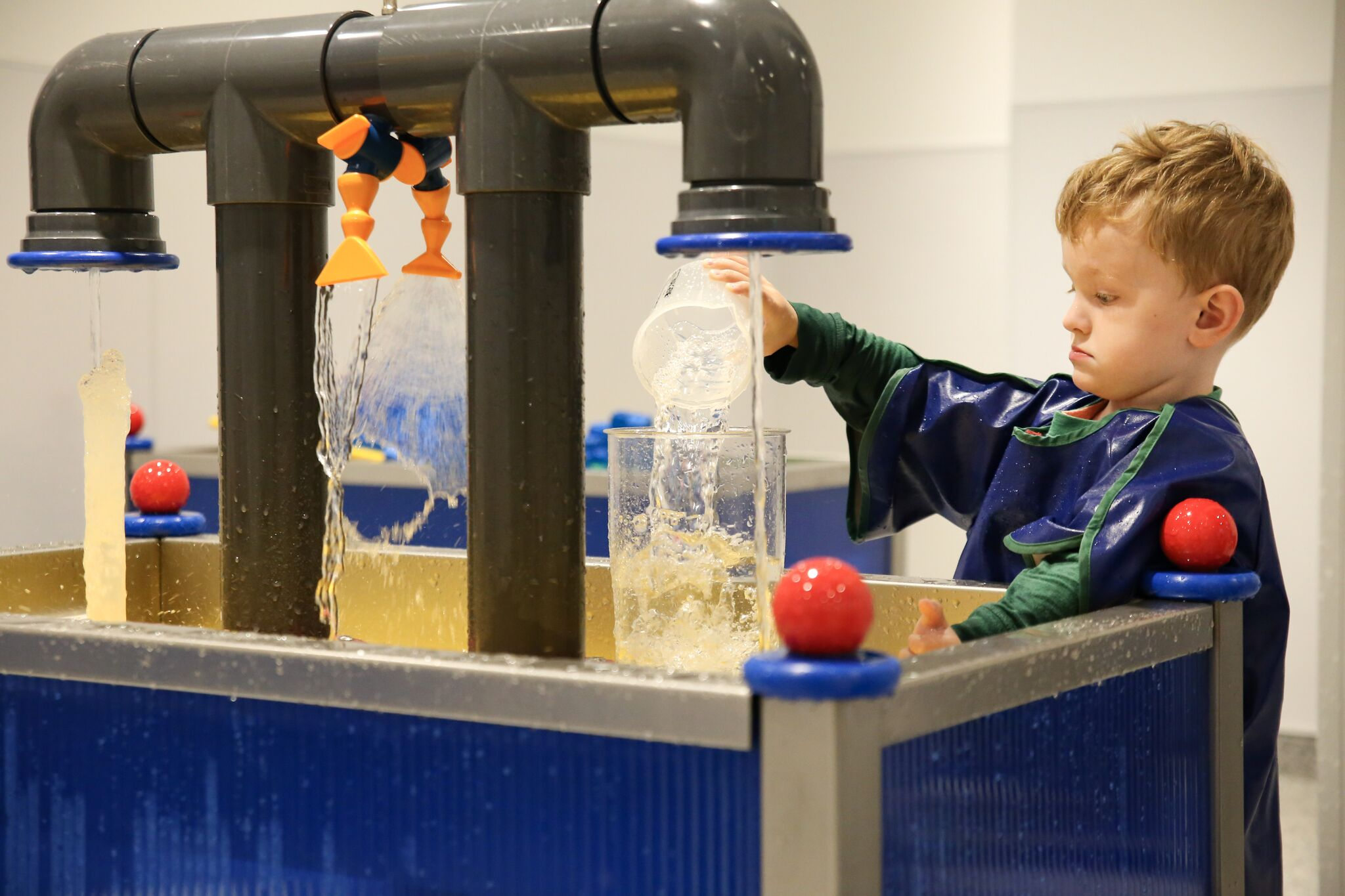 Young boy playing in the water gallery at the Discovery Museum