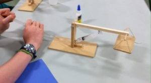 Teens build mini hydraulic lifts.
