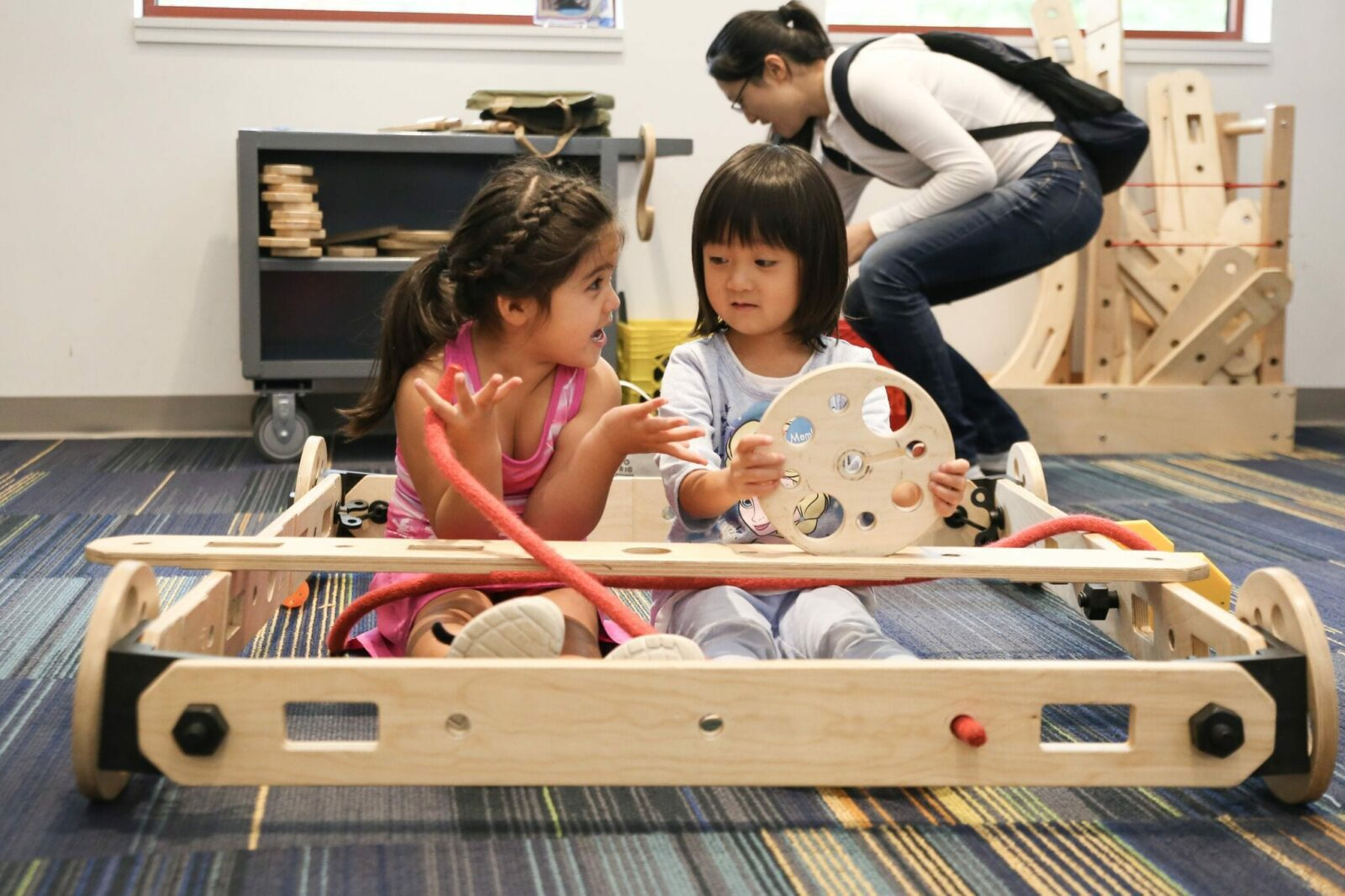 Two young girls playing with a wood contraption at the Discovery Museum