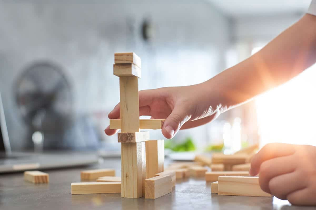 Hand_of_kid_playing_a_blocks_wood_tower_game_of_architectural_project