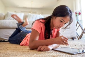 een_lying_on_floor_doing_schoolwork_on_tablet
