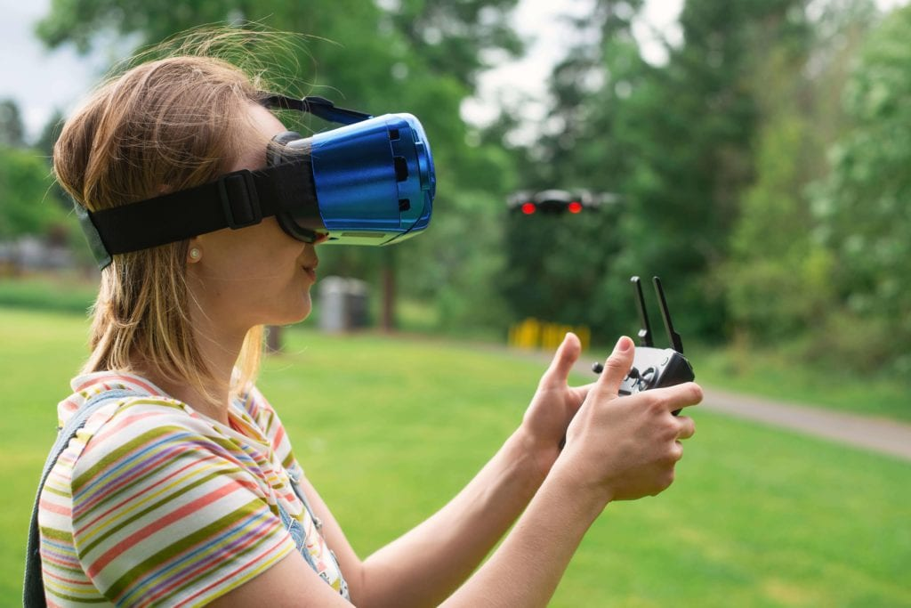 girl controls a drone in the park with the help of a VR helmet