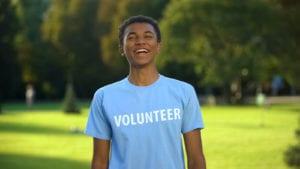 male_teen_volunteer_standing_outside