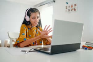 Teenage_girl_with_headphones_talking_and_working_on_laptop