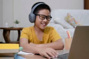 cheerful boy using computer for online instruction