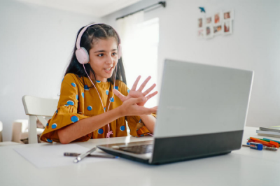 Teenage girl with headphones talking and working on laptop